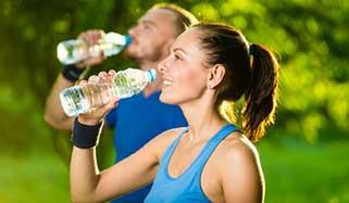 Homme et femme sportifs buvant