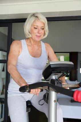 femme sur vélo en salle de gym